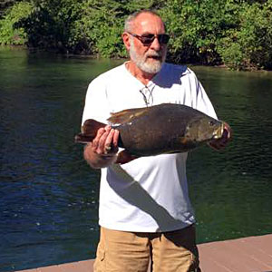 Bruce Kraemer caught this giant 9.98 pounds Michigan smallmouth bass fishing from shore on the Indian River with a live nightcrawler on a three-way rig.