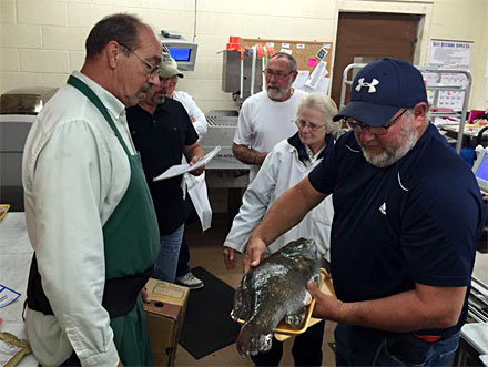 Bruce Kraemer (Center rear) looks on as his giant smallmouth bass is prepared for the official weigh in.
