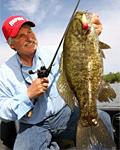 Minnesota bass fishing ace Scott Bonnema shows off a big post-spawn smallmouth bass that fell for a topwater popper