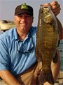 Captain Wayne Carpenter shows one of many big smallmouth bass he has caught from Lake St. Clair